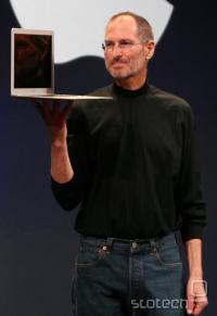 Steve Jobs s svojimi značilnimi očali, črnim pulijem in kavbojkami z MacBook Airom v roki