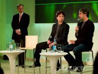 Vodilna trojica - Eric Schmidt, Sergey Brin in Larry Page z mikrofonom v roki